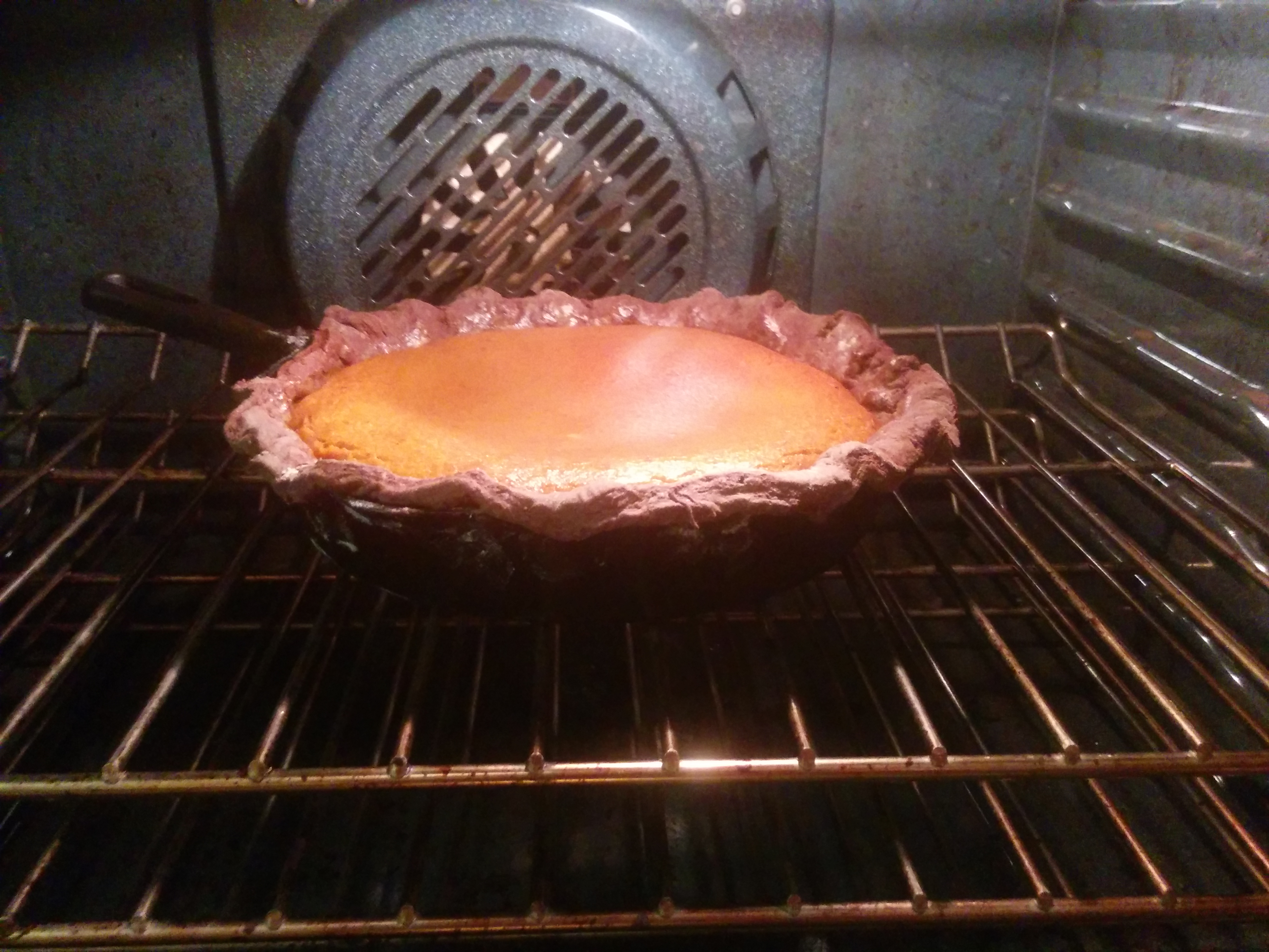 Pumpkin pie in the over in a cast iron pan